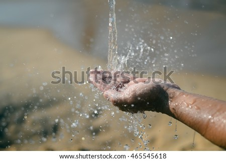 Close up of human hand catching water, ocean beach outdoors background
