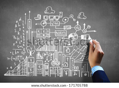 Close up of human hand drawing business plan with chalk - stock photo