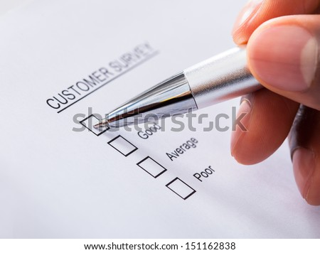 Close-up Of Human Hand Filling Customer Survey Form - stock photo