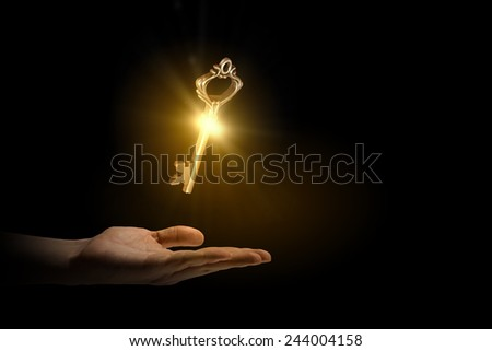 Close up of human hand holding golden key - stock photo
