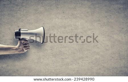 Close up of human hand holding megaphone - stock photo