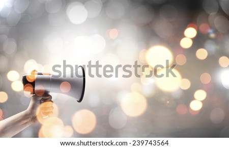 Close up of human hand holding megaphone - stock photo