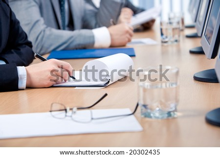 Close-up of human hand holding pen and writing a plan during corporate work