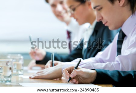 Close-up of human hand holding pen over paper on background of working people - stock photo