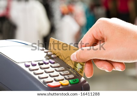Close-up of human hand holding plastic card in payment machine