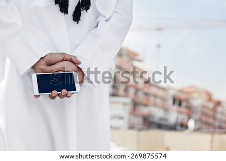 Close Up Of Human Hand Holding Smart Phone Near Reconstruction Area - stock photo