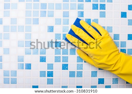 Close up of human hand in yellow glove. The cleaner is washing tile in bathroom with a wisp - stock photo