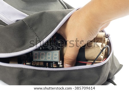 Close-up of human hand placing time bomb in bag. - stock photo