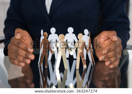 Close-up Of Human Hand Protecting Cut-out Figures - stock photo