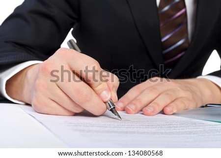 Close up of human hand signing a document - stock photo