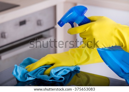 close up of human hand with protective gloves cleaning induction hob with rag and holding spray