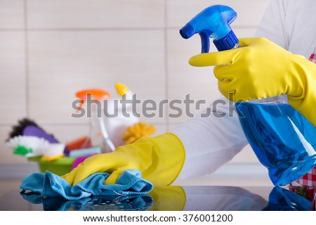 Close up of human hand with protective gloves cleaning induction hob with rag. Cleaning supplies in background - stock photo