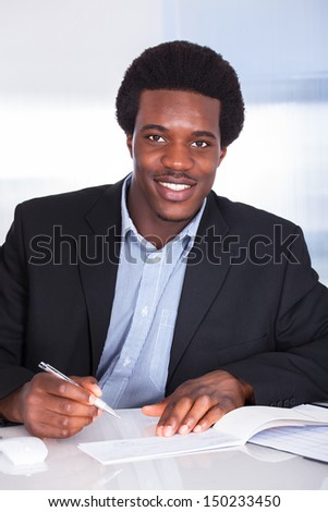 Close-up Of Human Hand Writing On Cheque - stock photo