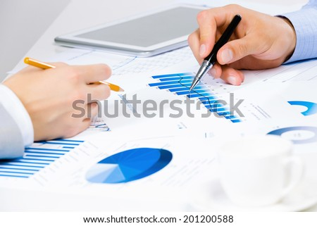 Close up of human hands and documents with graphs and diagrams - stock photo