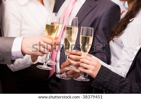 Close-up of human hands cheering up with flutes of sparkling champagne - stock photo