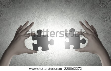 Close up of human hands connecting puzzle elements