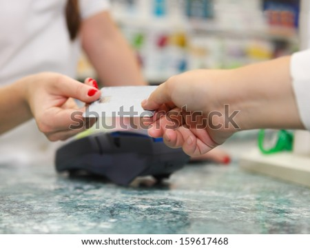 Close up of human hands holding credit card in drug store - stock photo