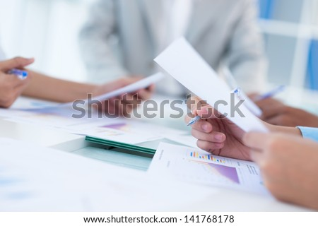 Close-up of human hands holding documents at the business conference - stock photo