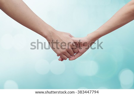 close up of human hands holding together for helping/encourage:handshake concept :family and friends concept.hand of power family.abstract lovers hand shake on blur light blue background with bokeh. - stock photo
