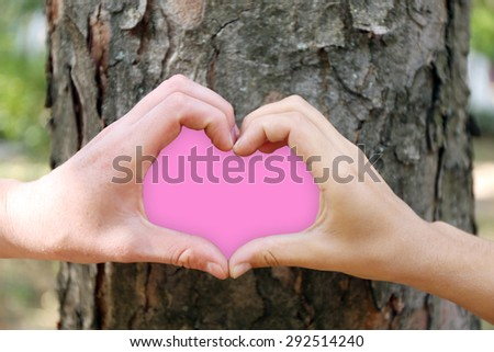 Close-up of human hands making heart shape in front of tree - stock photo