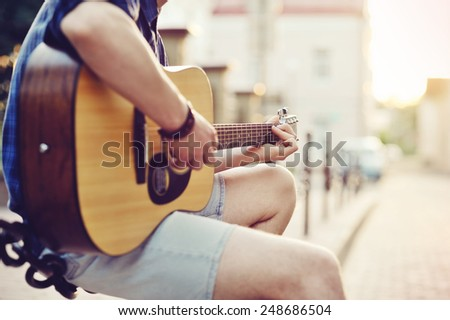 Close up of human hands playin guitar  - stock photo
