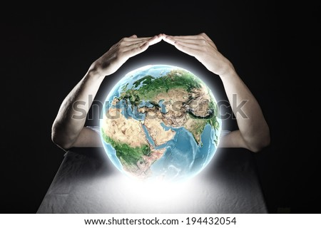 Close up of human hands protecting Earth planet. Elements of this image are furnished by NASA - stock photo
