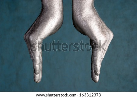 close-up of human hands represent a form of bowls or flower on blue-gray background, side view