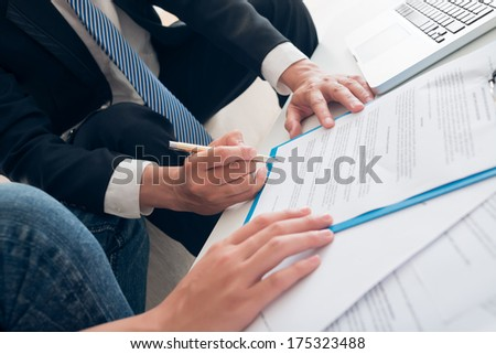 Close-up of human hands signing an important contract at the office on the foreground  - stock photo