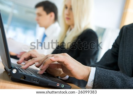 Close-up of human hands typing on laptop keyboard with working people at background - stock photo