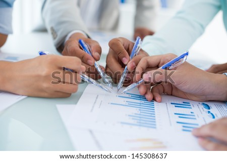Close-up of human hands with ballpoints pointing at the graphs