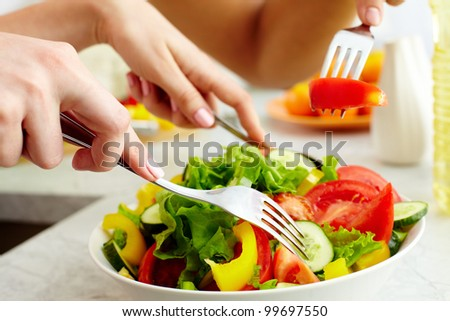 Close-up of human hands with forks tasting salad