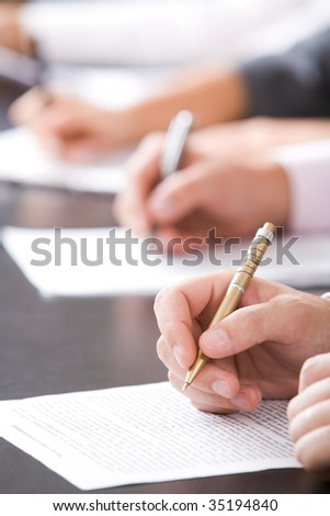 Close-up of human hands with pen over business document - stock photo