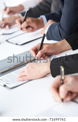 Close-up of human hands with pens over business documents