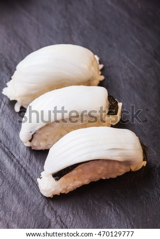 Close-up of Ica sushi with squid on a black slate background