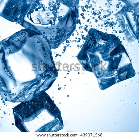 close up of ice cubes and bubbles in water on white background - stock photo