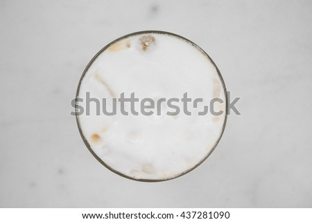 close up of iced cold milk latte of cappuccino cup with white marble table top as blurred background - top view