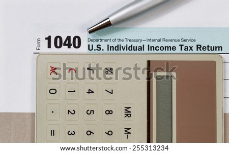 Close up of income tax form, silver pen and calculator with gray folder underneath. Business financial concept.  - stock photo