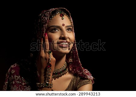 Close-up of Indian bride in wedding attire and jewelery