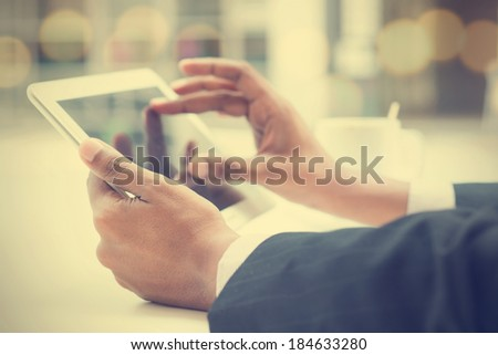 Close-up of Indian male hands touching digital tablet, formal businessman with cup of coffee on table. - stock photo
