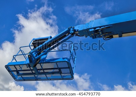 Close up of industrial boom lift basket against blue sky.