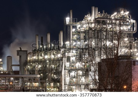 Close-up of industrial pipelines and  bubble towers of an oil-refinery plant in the night
