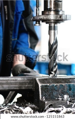 Close-up of industrial worker drilling a hole in a metal bar