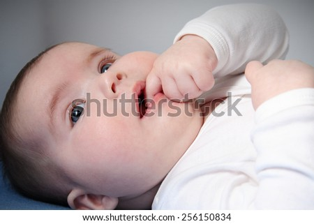 Close up of infant sucking finger - stock photo
