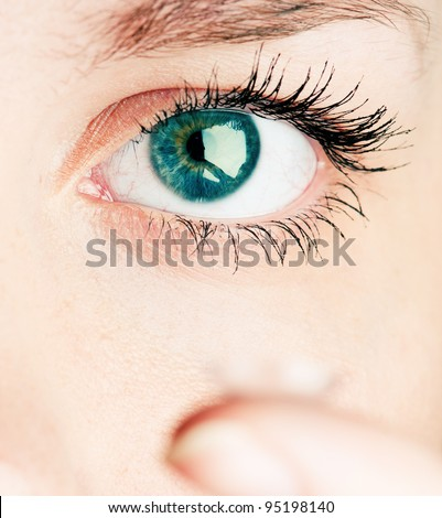 Close up of inserting a contact lens in female eye - stock photo