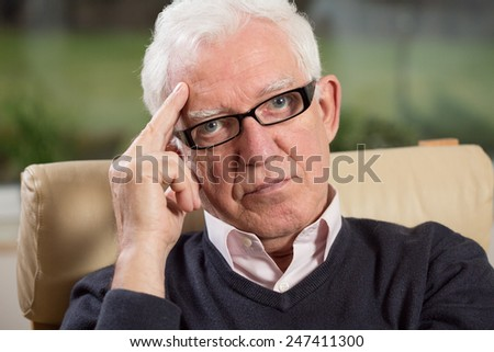 Close-up of intelligent elder man wearing glasses - stock photo