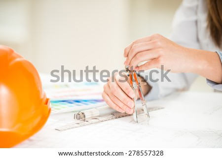 Close-up of interior designer working with architectural plan with compass. - stock photo