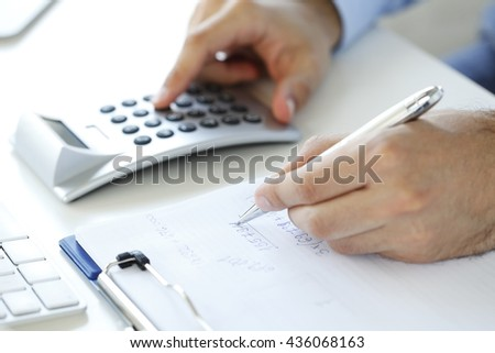 Close-up of investment advisor calculating expenses while sitting at office in front of computer.