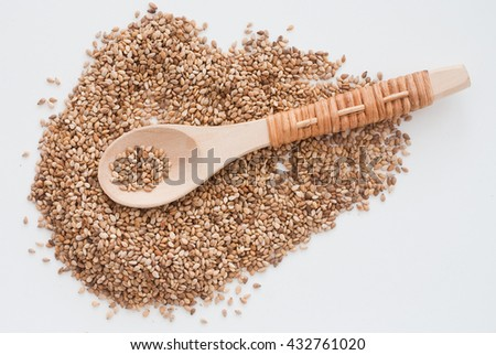 close up of isolated sesame on white background - traditional wooden spoon - studio shot from above - stock photo