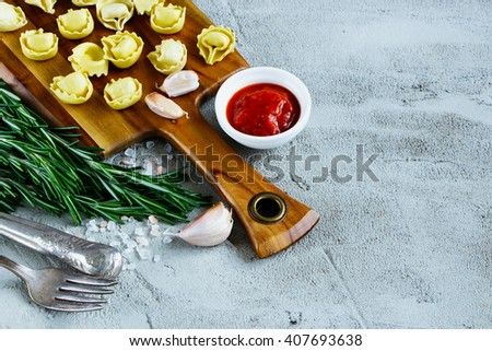 Close up of italian food background with wooden cutting board, homemade raw tortellini, tomato sauce and rosemary over concrete textured board, place for text, border, selective focus. - stock photo