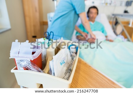 Close up of IV cart with nurse and patient in background - stock photo